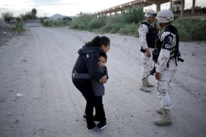 Guatemalan migrant Ledy Pérez embraces her son Anthony as she pleads with Mexican armed police