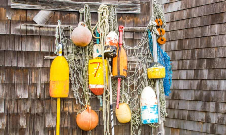 Lobster buoys and fishing net hanging on the wall of a weathered fishing shack in Massachusetts