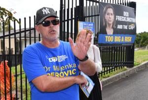 An LNP booth worker (left) is seen reacting towards Queensland Premier Annastacia Palaszczuk