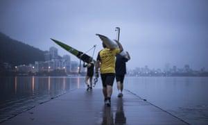 Rowers carry boats at the Rodrigo de Freitas Lagoon in Rio de Janeiro.