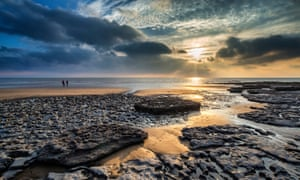 sunset over rocks and sand Dunraven Bay