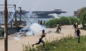 Egyptians run for cover from teargas during clashes with security forces on the Nile island of Warraq