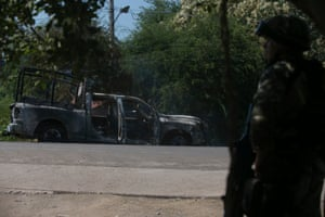 A soldier stands by a charred truck that belongs to Michoacan state police, after it was burned during an attack in El Aguaje, Mexico, on 14 October. At least 13 police officers were killed and three others injured Monday in the ambush.