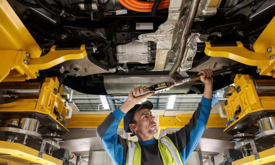 A worker adjusts the wheel alignment on a TX electric black cab at a plant in Coventry