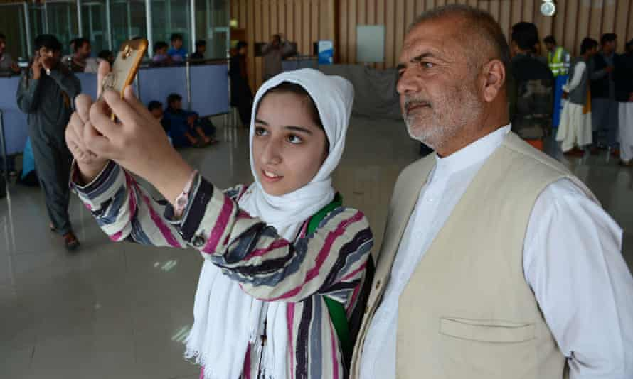Fatima Qaderyan takes a photo with her father at Herat airport last month.