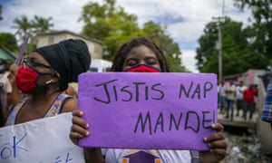 A protester holds up a sign that reads in Creole 'We are asking for justice', during Yves Jean-Bart's meeting with the local district attorney last week.