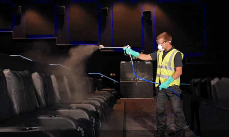 A man in a hi-vis tabard spraying cinema seats with cleanser
