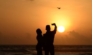 Couple taking a picture on the beach at sunset in Sri Lanka