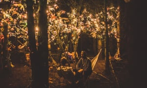 People chilling in the woods, a seated man wearing a crown, Farr Festival, Hertfordshire.