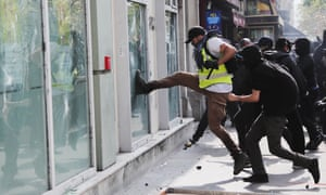 A gilets jaunes protester kicks at the window of a bank in Paris