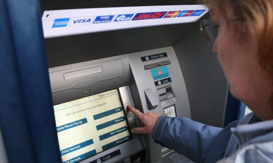 A woman uses a Barclays cash machine