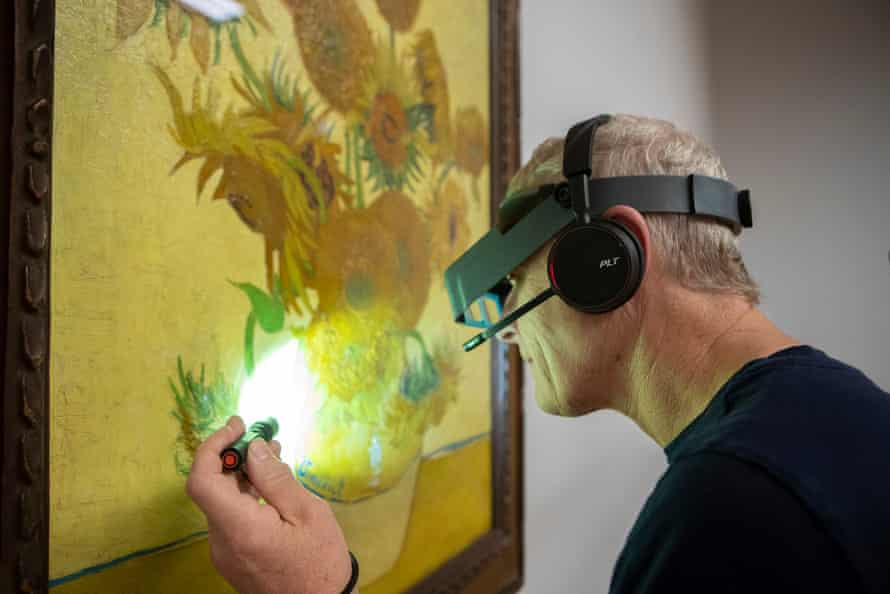An NGA painting conservator inspects Vincent van Gogh's Sunflowers