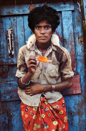 A teenage boy with an albino rat, Chennai, India, 1996
