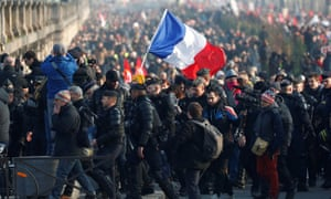 Workers hold a French flag in Paris during a demonstration against pension reforms