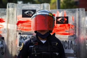 A riot police officer with a painted visor in Mexico City, Mexico