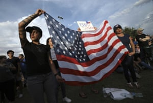 El Paso, Texas: Twins Jessica Torres, left, and Danielle Novoa hold an American flag during a vigil at the the Hope Border institute