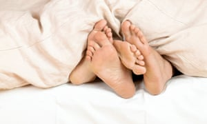 A couple is lying in bed