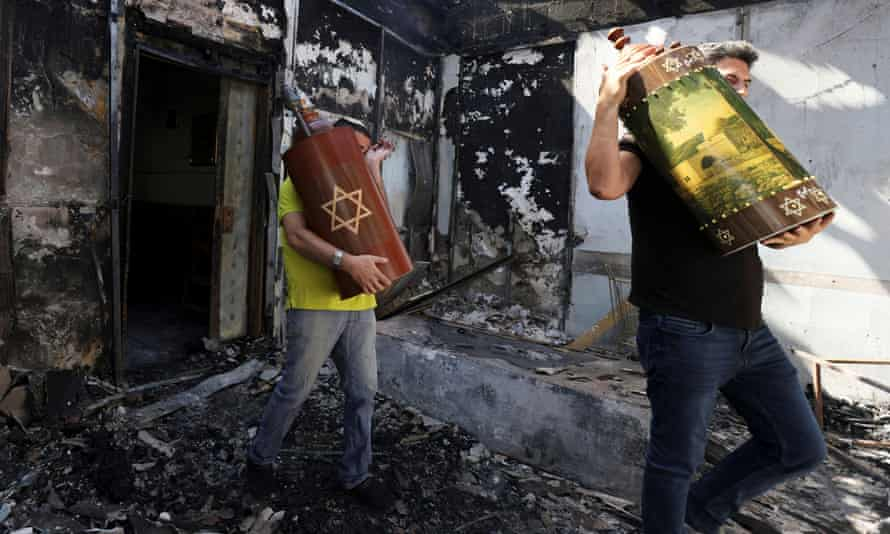 Torah scrolls, Jewish holy scriptures, are removed from a synagogue set on fire during violent confrontations in the city of Lod