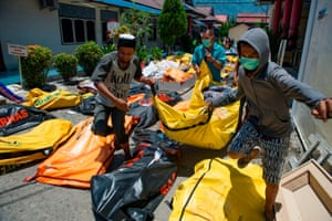 Family members carry the body of a relative to the compounds of a police hospital in Palu.