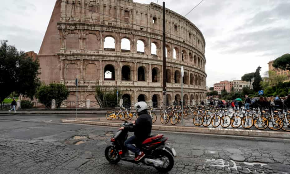 A motorcyclist rides over some of Rome's 10,000 potholes on a road by the Colosseum.