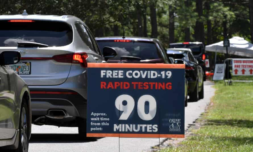 People in cars wait at a Covid testing and vaccination site at Barnett Park in Orlando, Florida.