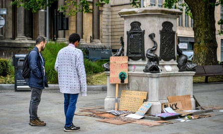 People read signs and placards at the base of the Edward Colston statue plinth in Bristol city centre, 10 June, 2020.