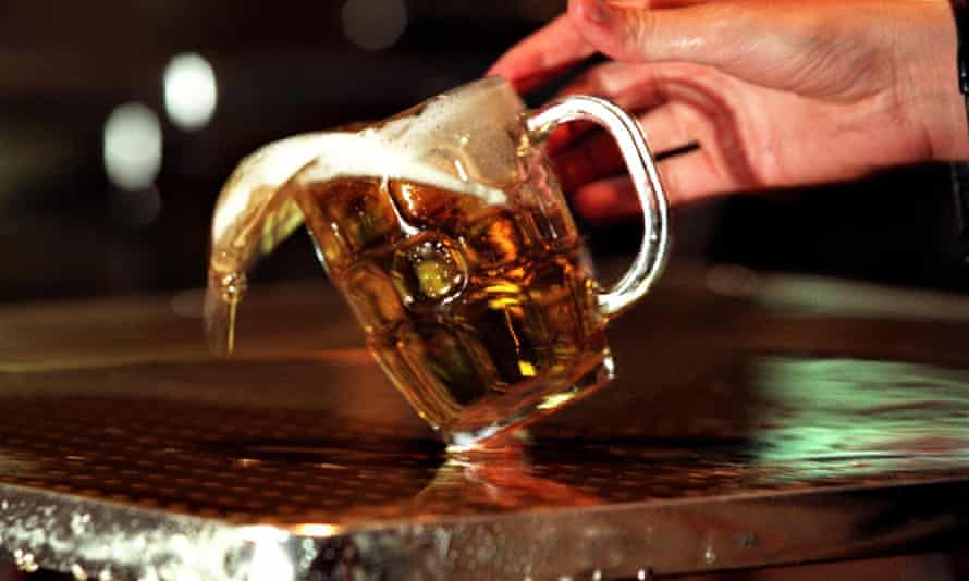 A pint of beer being spilled on a pewter bar