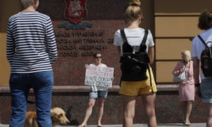 A woman holds a poster reading 'Take away your drugs, return freedom to Golunov' in Moscow, Russia