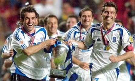Georgios Karagounis, left, and Theodoros Zagorakis of Greece run with the Euro 2004 trophy