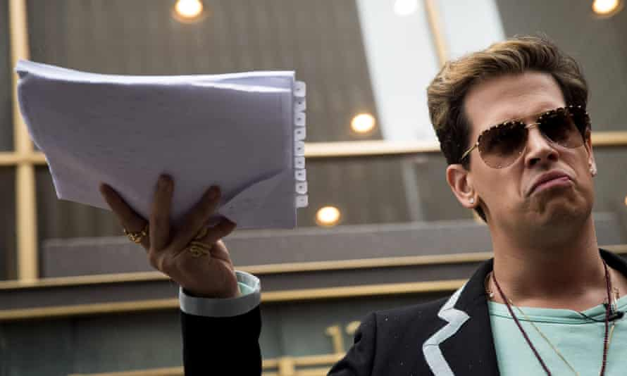 Milo Yiannopoulos holds up a copy of his legal complaint outside Simon & Schuster's New York office in July 2017.