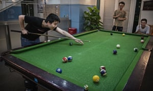 Employees play pool after work at a recreation area in staff housing at the Bantian campus