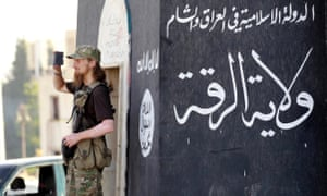 A fighter films an Isis military parade in Raqqa province, Syria