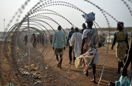 Tuesday, Jan. 19, 2016, displaced people walk next to a razor wire fence at the United Nations base in the capital Juba, South Sudan.