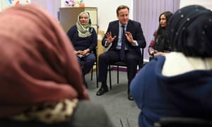 David Cameron speaks with women attending an English language class.