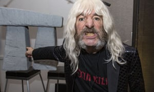 Harry Shearer as Spinal Tap bassist Derek Smalls with a miniature model of Stonehenge.