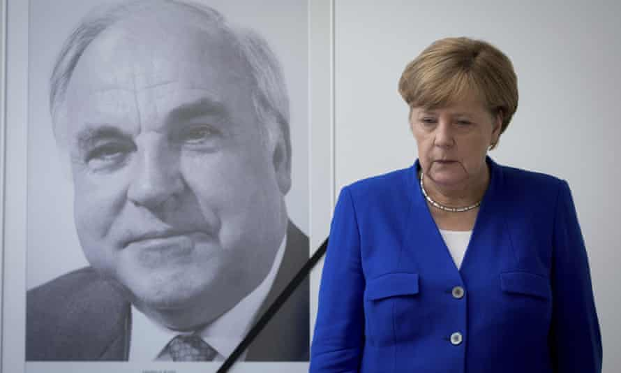 Angela Merkel looking sombre next to a big photo on the wall of Helmut Kohl