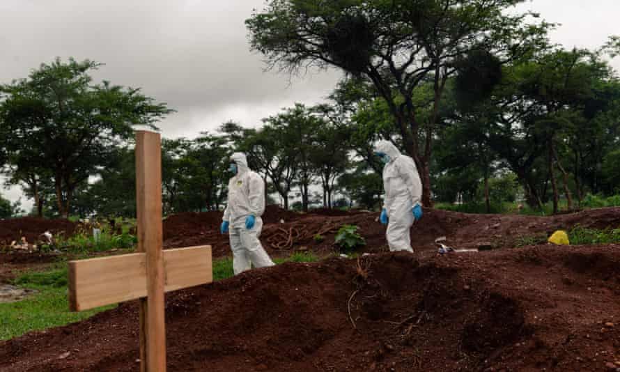 Undertakers in PPE inspect a grave site where a person that passed away due to Covid is to be buried in Zimbabwe.
