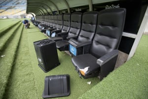 A rubbish bin lays by ripped seats in one of the dugouts.