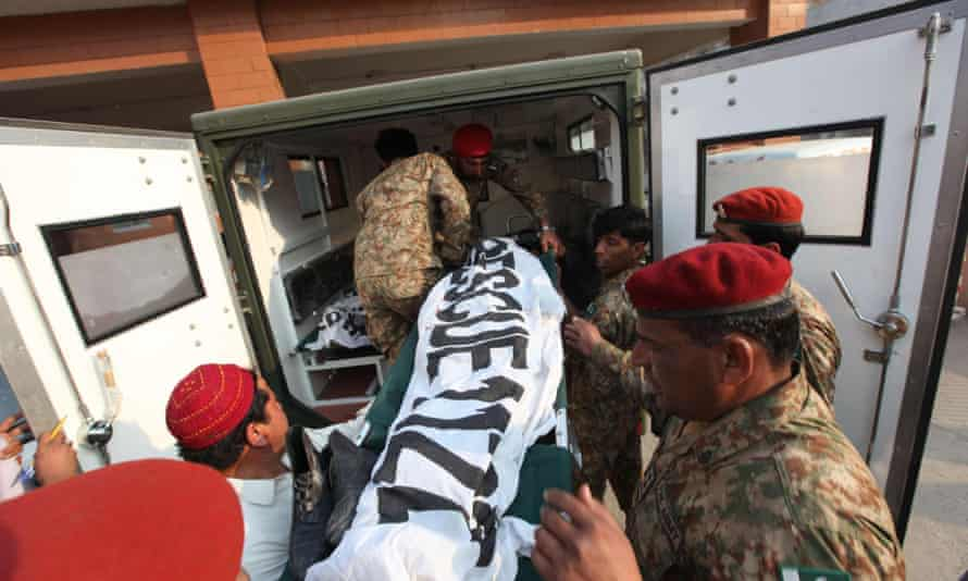 Pakistani soldiers moving bodies