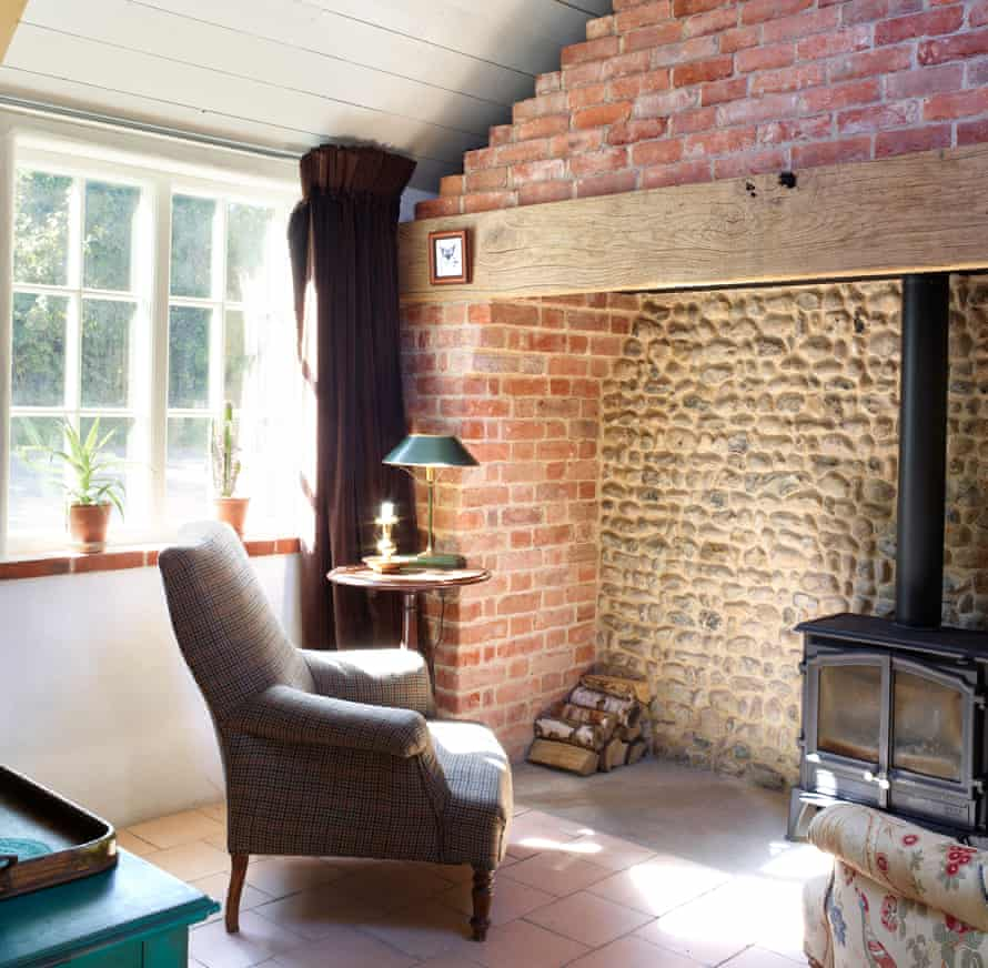 Vintage fabrics and furniture work alongside traditional building materials, including original flint walls and new Norfolk pamments.