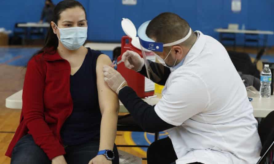 Teacher Lizbeth Osuna receives a Moderna Covid-19 vaccine from Walgreens pharmacist Peter Shinneck Chicago.