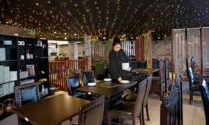 Seveni Bar and Restaurant, showing the ceiling covered in rows of fairy lights and a waitress laying a table