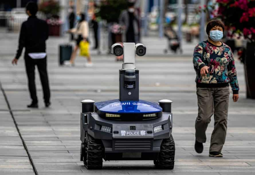 A police security robot drives on the high-speed railway station platform in Shenzhen, Guangdong province. The device, which patrols public places, warns people when they are not wearing masks, checks their body temperature and identity.