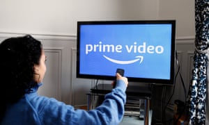 a girl turns on the TV displaying an Amazon Prime Video logo