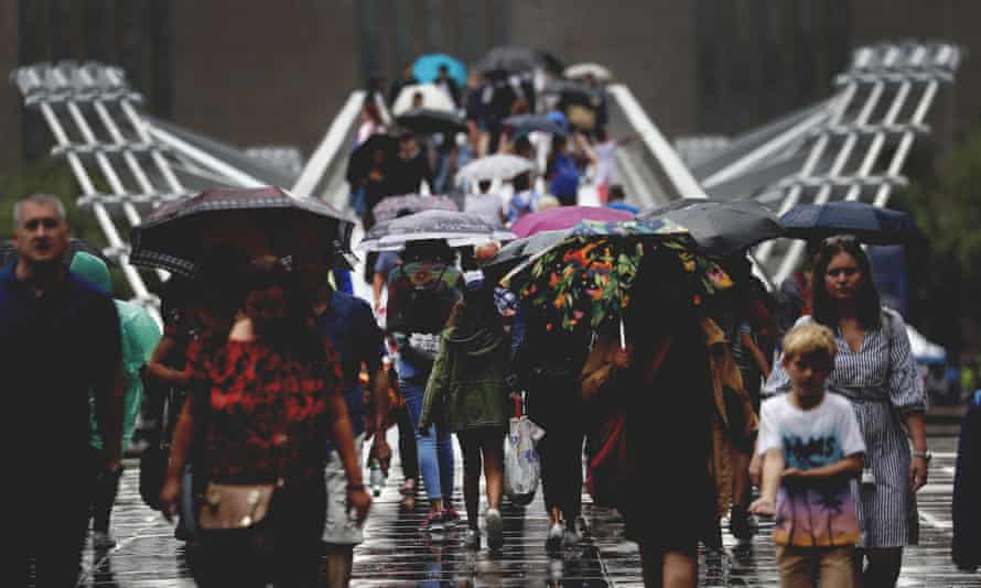 People cross the Millennium Bridge in London in the rain.