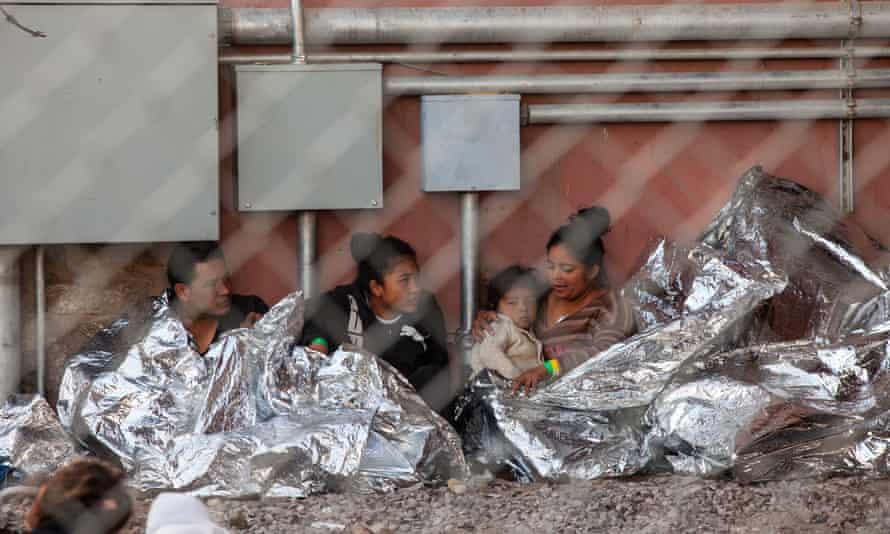 Migrants wait under blankets.