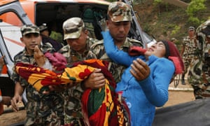A victim with a broken leg is carried by Nepalese soldiers as she arrives by helicopter from the heavily-damaged Ranachour village