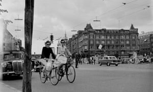 A street view of local girls riding their bicycles in Copenhagen, Denmark.