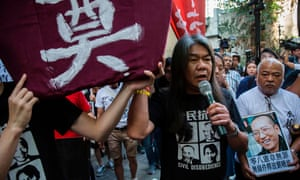 Pro-democracy protester Leung Kwok-hung joins a march in Hong Kong on Saturday. He was later taken away by police.