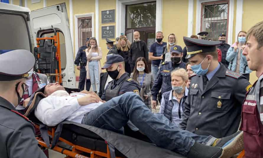 Police officers and paramedics carry Stepan Latypov, after he stabbed himself in the neck with a pen during a court hearing on 1 June.
